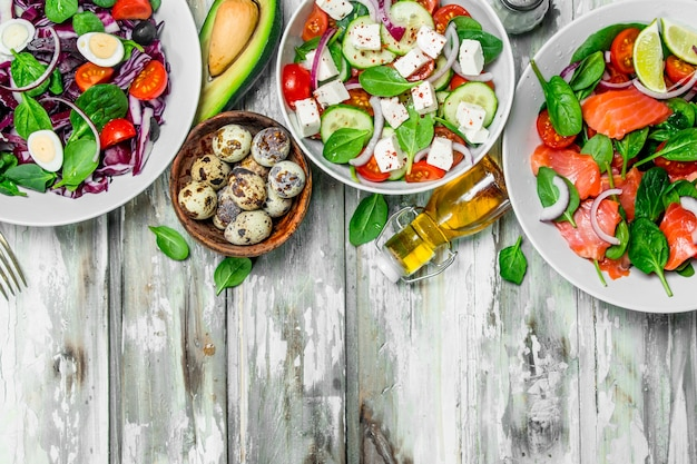 Различные салаты из органических овощей, рыбы и сыра с оливковым маслом и специями на деревенском столе.
