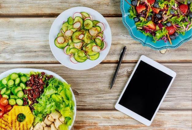 タブレットと木製のテーブルの上にペンで様々なサラダ