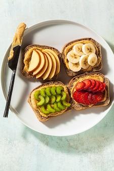 땅콩 버터와 딸기, 셀러리, 바나나와 사과 테이블에 접시에 다양한 샌드위치. 완벽한 아침 식사