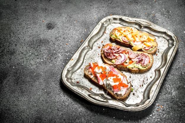 레드 캐비어, 베이컨, 치즈, 신선한 야채를 곁들인 다양한 샌드위치.