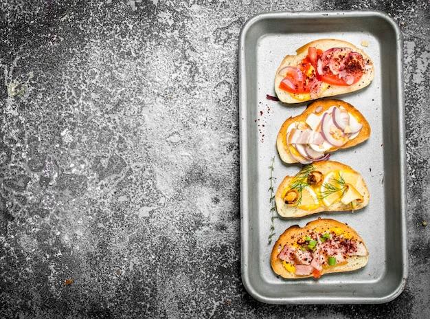 素朴なテーブルのスチールトレイに赤キャビア、ベーコン、チーズ、新鮮な野菜のさまざまなサンドイッチ。