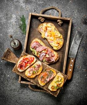 오래된 쟁반에 해산물, 고기 및 야채와 함께 다양한 샌드위치. 소박한 테이블에.