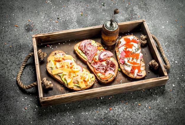 오래된 트레이에 해산물, 고기 및 야채가 들어간 다양한 샌드위치