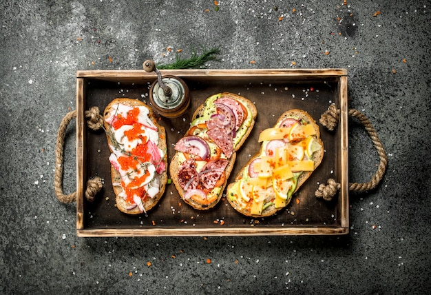 素朴なテーブルの上の古いトレイにシーフード、肉、野菜のさまざまなサンドイッチ。