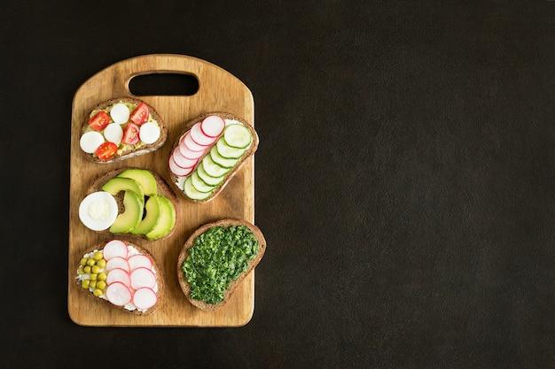 Различные бутерброды с овощами на разделочной доске, плоской, лежат на темном бетоне