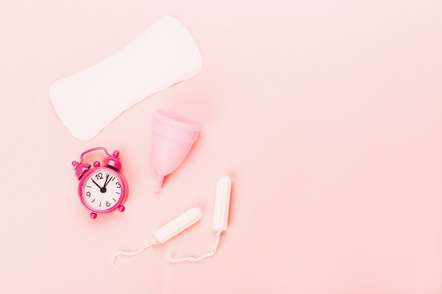 Various sanitary products on pastel pink background.