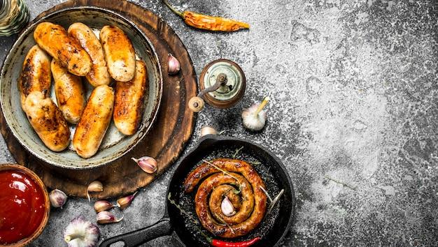 素朴なテーブルにニンニクとスパイスを入れた鍋にさまざまなソーセージ。