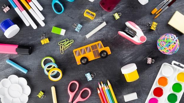 Различные школьные принадлежности и принадлежности для рисования на черном фоне. снова в школу концепции. вид сверху