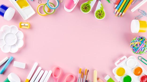 ピンクの背景の様々な学校のオフィスや絵画用品。学校のコンセプトに戻る。上面図。コピースペース