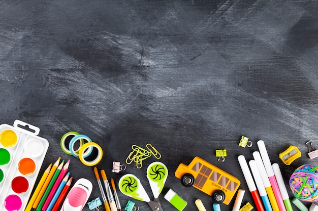 Various school office and painting supplies on black background. back to school concept. top view. copy space