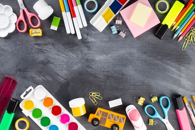 Various school office and painting supplies on black, flat lay