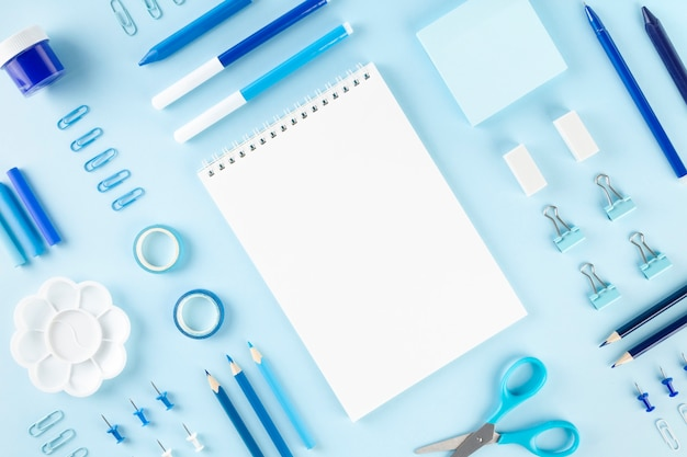 Various school office and painting supplies on blue background. back to school concept. geometric and monochrome composition. top view. copy space