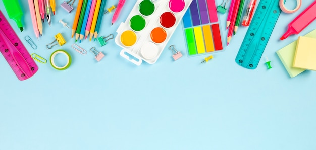 Various school office and painting supplies on blue background. back to school concept.