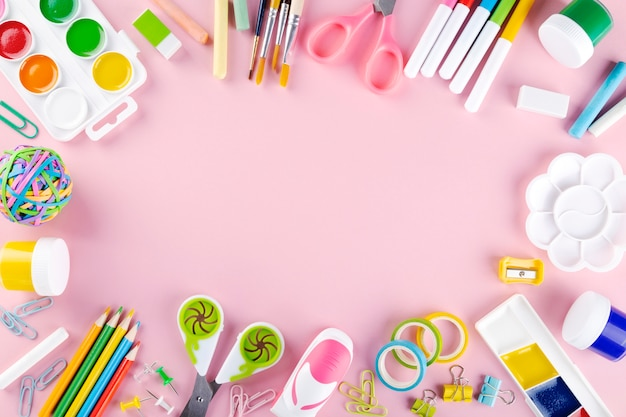 Various school office and painting supplies on pink background. back to school concept. top view. copy space