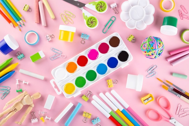 Various school office and painting supplies on pink background.