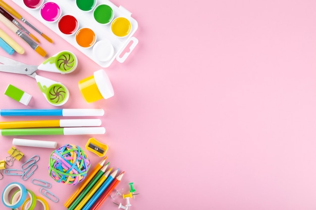 Various school office and painting supplies on pink, flat lay
