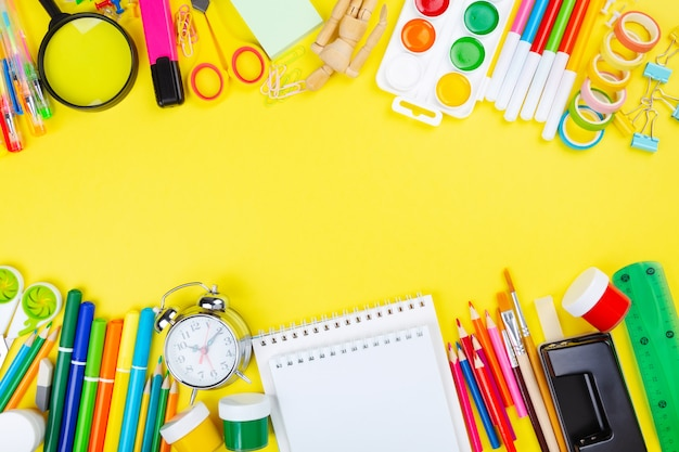 Various school office and painting supplies on yellow background