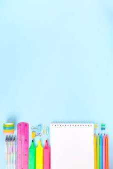 Various school office supplies on blue background. back to school concept.
