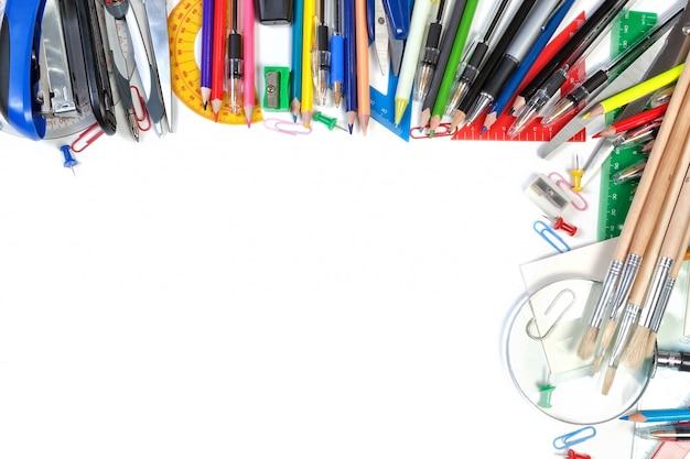 テキストのフレームにさまざまな学用品。白い壁の上。