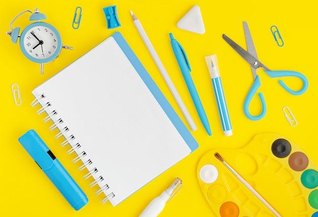 Различные школьные принадлежности на живой желтой предпосылке. копирование пространства, вид сверху