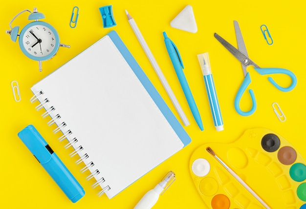 Various school supplies on vibrant yellow background. copy space, top view