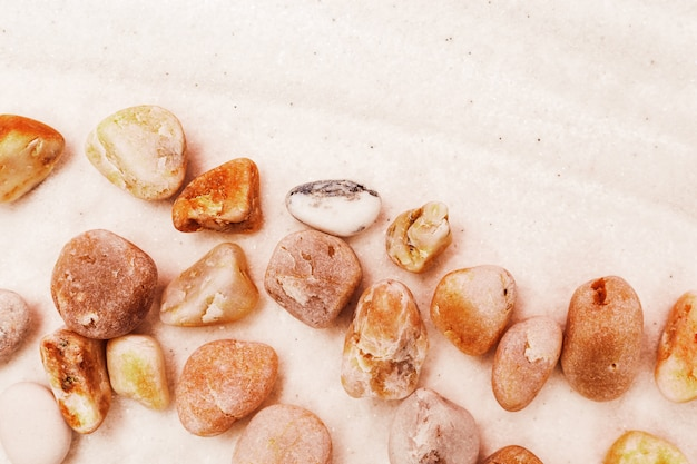 Various sea stones on beach. bright colored pebbles on sand.