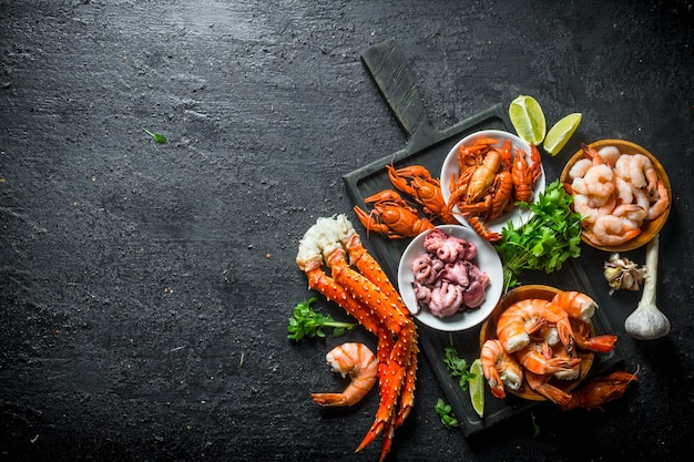 Various seafood on a cutting board with garlic, lime and parsley on black rustic table