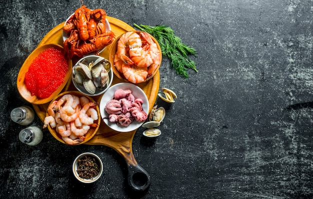 Various seafood on a round cutting board with herbs and spices.