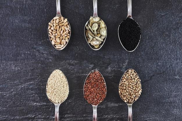 さまざまな種子の品揃え。ゴマ、ヒマワリ、カボチャ、亜麻、麻、ブラッククミンのスプーンのセット。