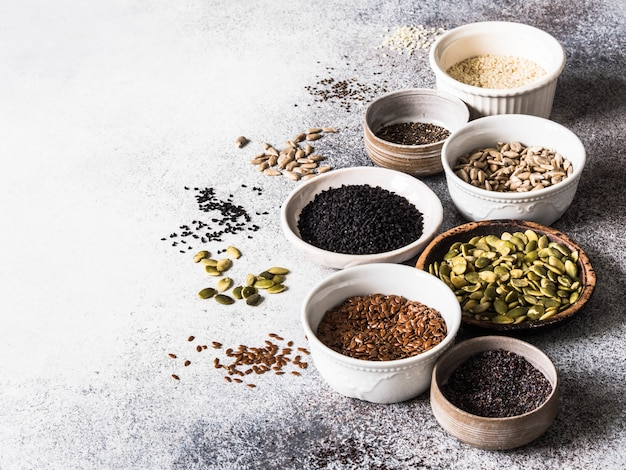 Various seeds - sesames, flax seed, sunflower seeds, pumpkin seed, poppy, chia in bowls on a gray background.