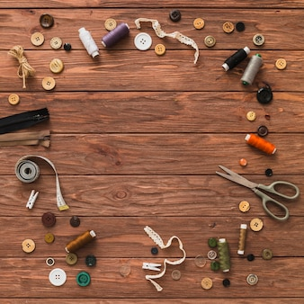 Various sewing accessories forming circle on wooden plank