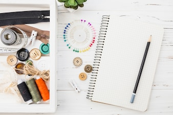 Various sewing accessories with notepad and pencil on wooden background