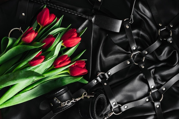 Various sex toys set on a black background. the view from the top. tulips. valentines day