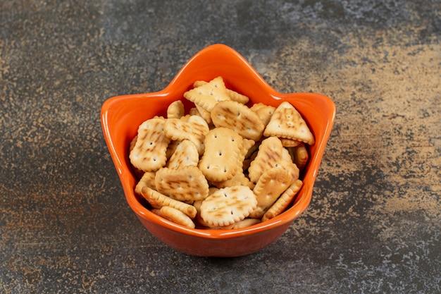 오렌지 그릇에 다양한 모양의 소금에 절인 크래커.