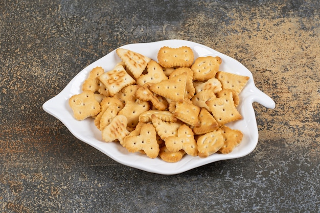 Cracker salati di varie forme su piatto a forma di foglia.