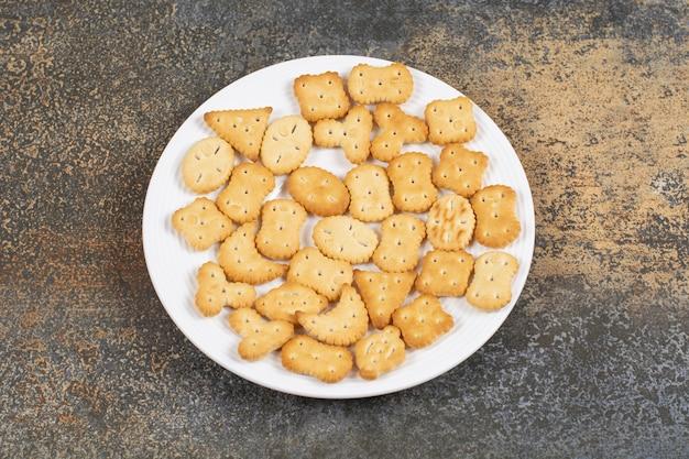 흰색 접시에 다양 한 모양의 소금에 절인 크래커입니다.