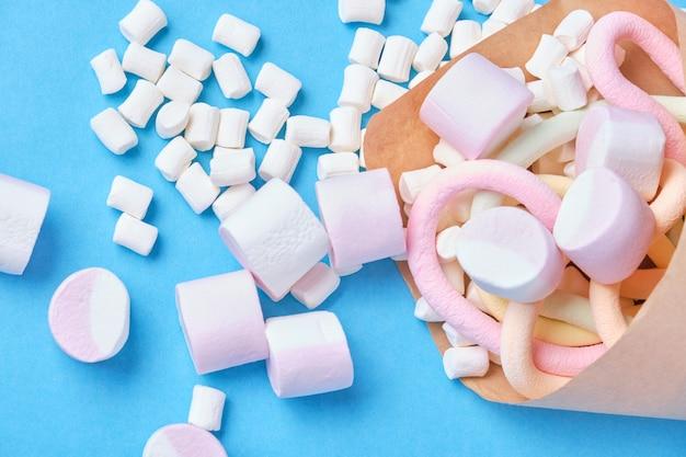 Различные формы зефира, завернутые в бумагу на синем фоне, крупный план, экологически чистая упаковка конфет, сладкая перкуссия