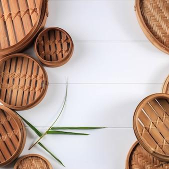 Различные размеры традиционной азиатской кухонной утвари бамбукового парохода на белом деревянном фоне. вид сверху, плоская планировка. скопируйте место для текста.