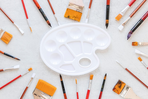 Various sizes of paint brush and white tray color palette