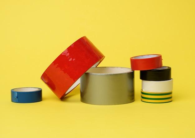 Различные мотки разноцветного скотча и изоленты на желтом фоне