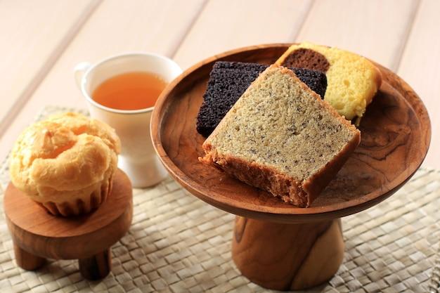 Различные кусочки торта для индонезийской коробки для закусок. заварочный, банановый торт, мраморный пирог и черный липкий рисовый пирог. подается с чаем. копирование пространства на деревянном фоне