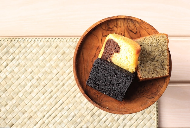 Various slice cake for indonesian snack box. banana cake, marble cake, and black sticky rice cake. top view with copy space for text