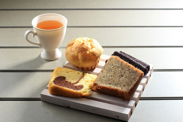 Various slice cake for indonesian snack box. choux, banana cake, marble cake, and black sticky rice cake. served with tea. copy space on wooden background