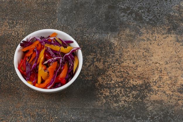 Различные нарезанные овощи в белой миске.