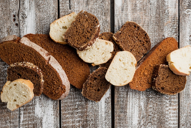 Various slices of loaf on wooden plank background top view