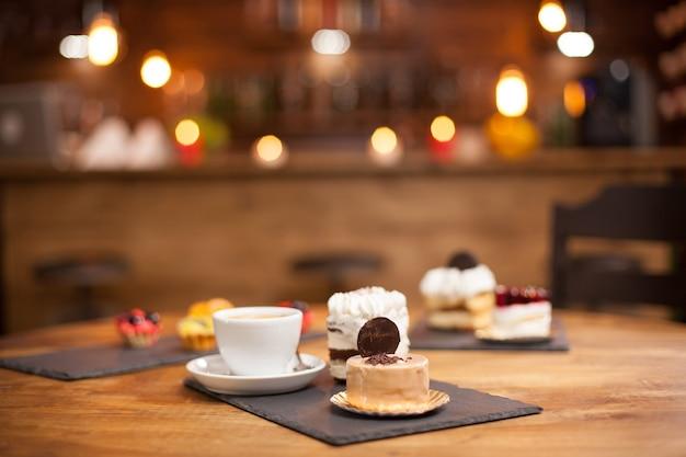コーヒーショップの木製テーブルに美味しいケーキのさまざまなスライス。上にビスケットをのせたおいしいケーキのスライス。おいしい一杯のコーヒー。