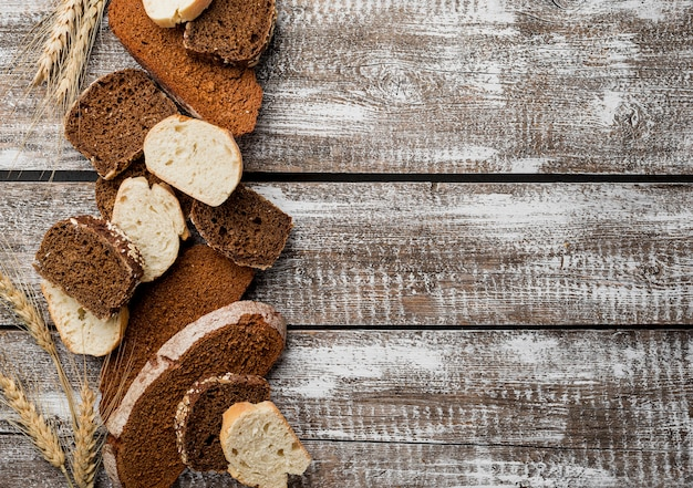 木製コピースペース板の背景にパンの様々なスライス