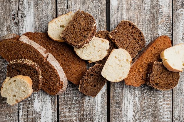 木の板の背景トップビューでパンの様々なスライス