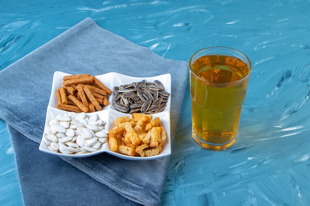 Various snack bowls next to glass of beer on a towel , on the blue surface.