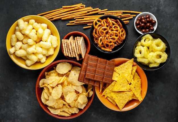 Различные закуски и шоколад на черном столе